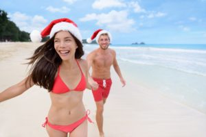 Happy Christmas couple having fun running on beach
